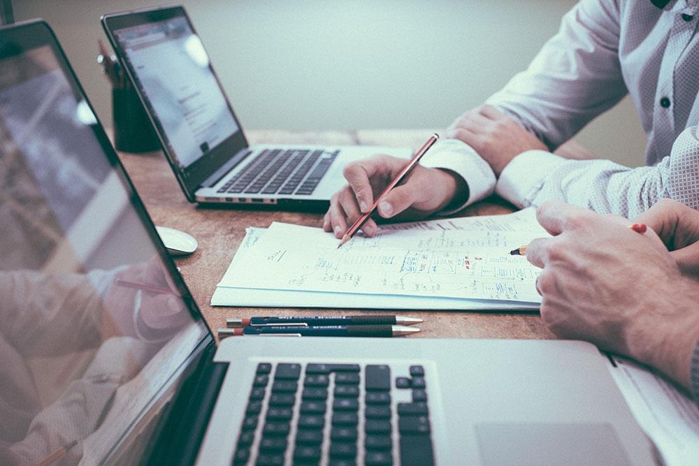 bureau avec 2 pc portable et 2 personnes en train d'écrire